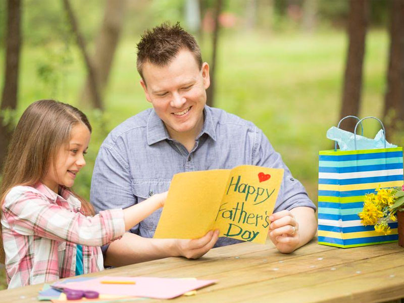 A sweet girl showing Father's Day greeting card to her Father