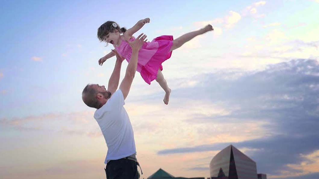 Daughter touching heights of sky with her father