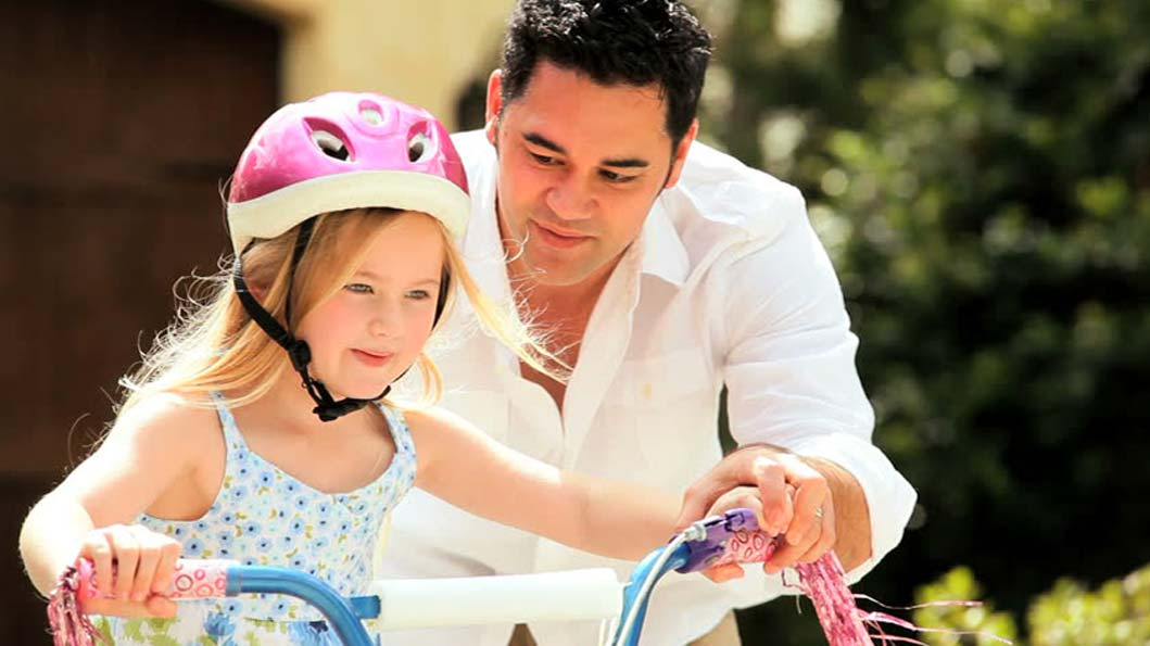 Father helping her daughter in learning how to ride toy wheel