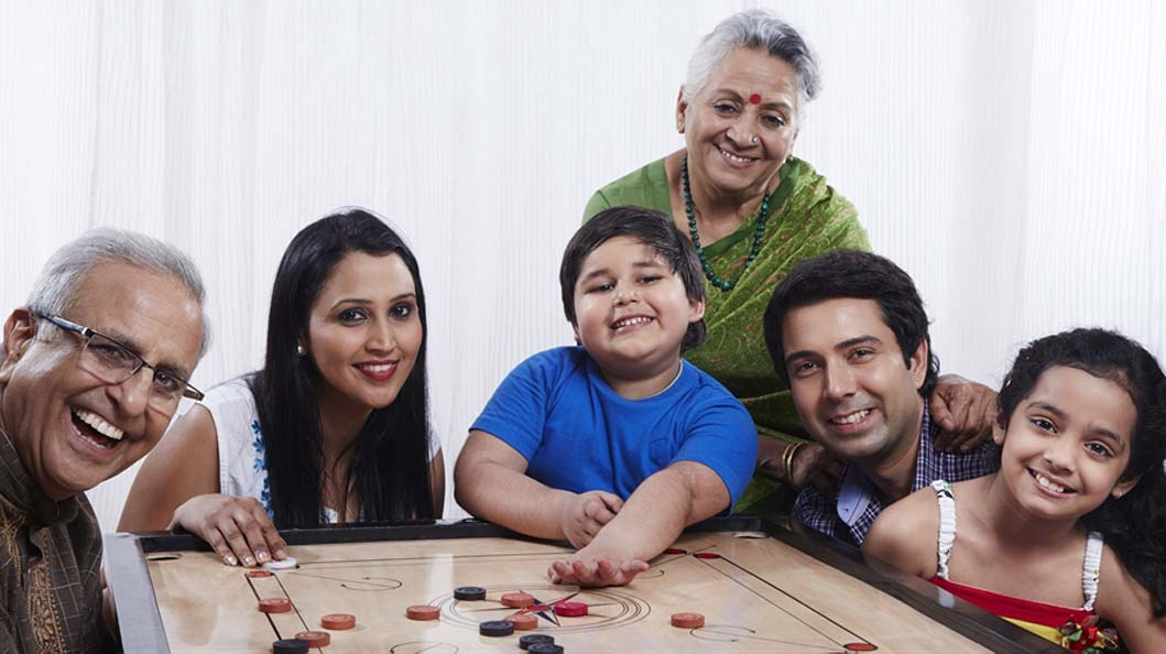 Family playing a carrom match together in appreciation of dad