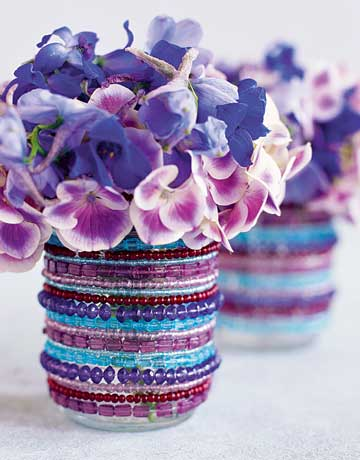 A bunch of flowers in a kitchen canister with purple beads